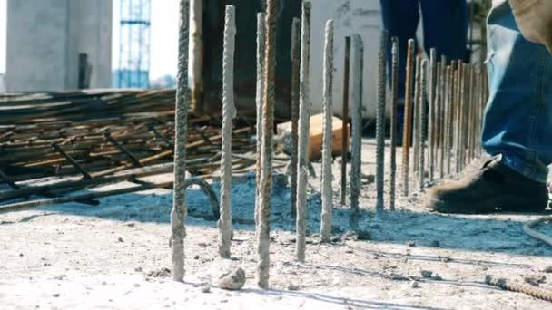 Mužský dělník buší do kovových stonků