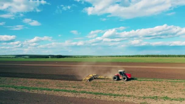 Moderní traktor pracuje na zemi, zasévání.