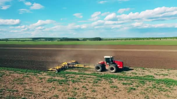 One tractor drives on a field, sowing seeds.