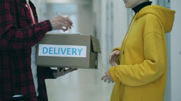 Kurýr dá krabici klientovi, který podepíše doručovací dokumenty
