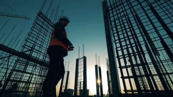Muž architekt se při západu slunce rozhlíží po staveništi