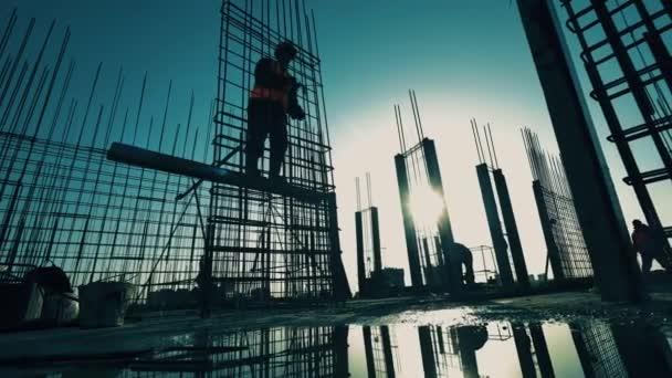 Bauindustrie, Bauprojekt, Bauprozess während des Sonnenuntergangs. Bauarbeiter bauen Metallgerüst eines Gebäudes
