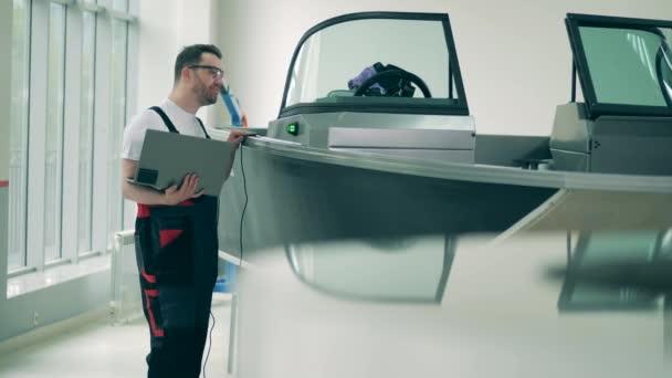 Mužský pracovník s laptopem kontroluje stav motorového člunu