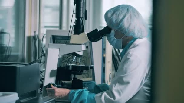 A pill is getting examined under a microscope by a pharmacologist