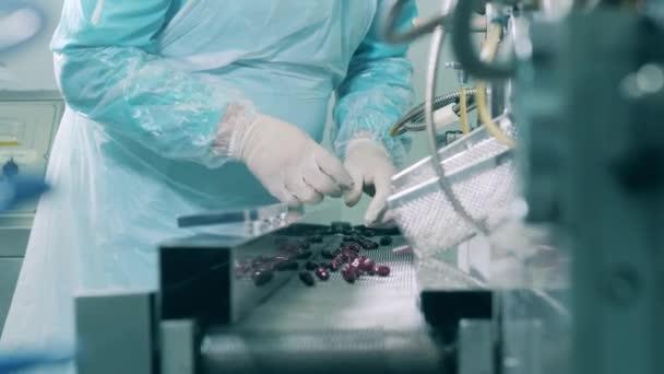 Pharmaceutics expert is observing pills of the conveyor