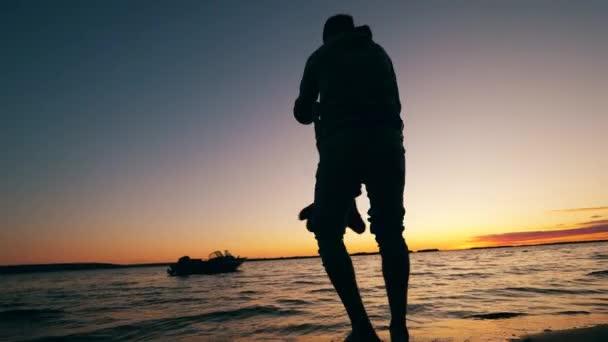 Egy gyereket megpörget egy apa a tó mellett.