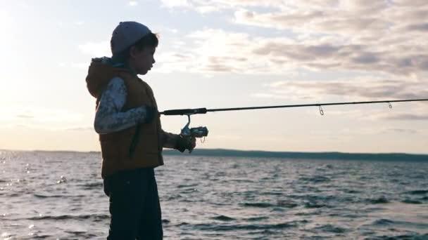 Egy fiú horgászbotot tart, miközben közel van a vízhez.