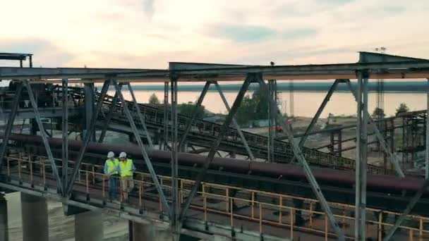 Průmyslová výstavba v přístavu se dvěma inženýry kráčejícími podél něj