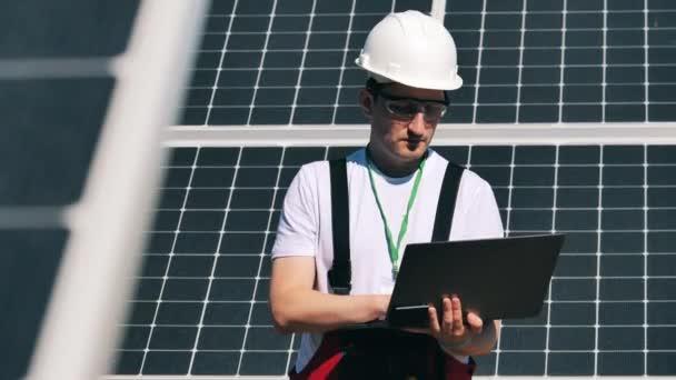 Techniker mit Laptop beobachtet Sonnenkollektoren. Arbeiter für alternative Energien in der Nähe von Solaranlagen.