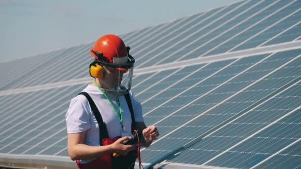 Napětí na solárních panelech kontroluje údržbář. Obnovitelná energie, solární elektrárna, koncept zelené elektřiny.