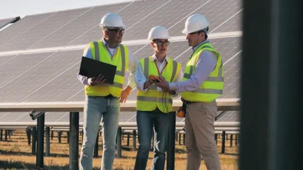 Obnovitelná energie, solární elektrárna, koncept zelené elektřiny. Skupina inženýrů stojí u solárních panelů a mluví