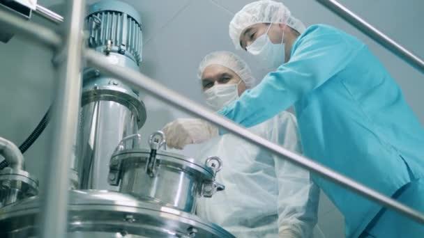 Muži v lékařských pláštích pracují se strojem v laboratoři.