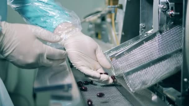 Pharmaceutical factory production line. Laboratory worker checks capsules falling on a conveyor.