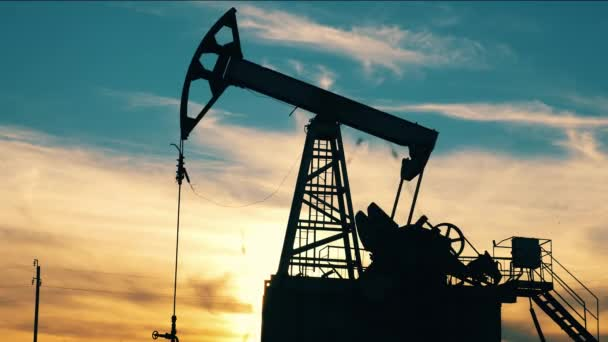 Pumping unit is extracting oil at sunset