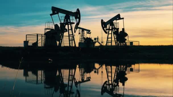 Olajkút, fúrótorony, olajmező, nyersolaj ára, olaj és gáz, olajhordó, olajipari koncepció.Olajkitermelés helyén több szivattyúzó egység naplementekor