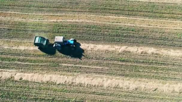 Pohled shora na traktor jedoucí podél pole a na senoseč