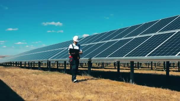 Údržbář s laptopem sleduje solární pole. Solární energie, solární panely, koncepce solární farmy.