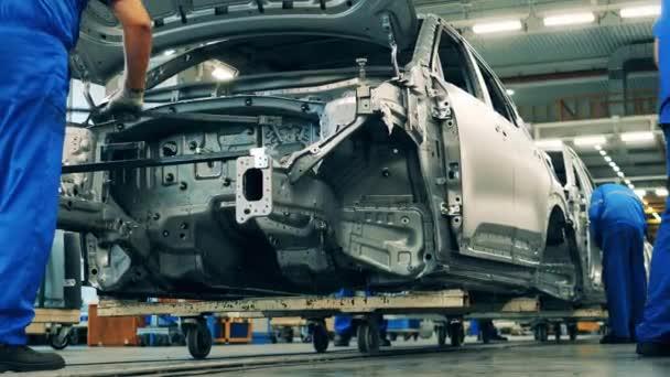 Mehrere Arbeiter montieren Autos am Fließband einer Autofabrik.