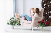Mladá maminka si hraje s její malé dítě v měkké křeslo v její velké a světlé místnosti