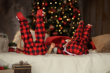 Two young children in red pajamas are lying on the bed, legs raised up and having fun. Christmas and New Year's family holiday
