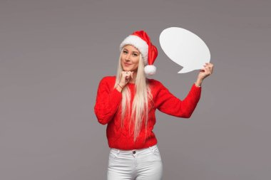 Portrait of surprised woman in Santa Claus hat  and knitted red sweater holding a white blank card with place for text. Gray isolated background
