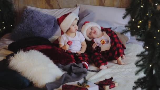 Kleine Kinder, Bruder und Schwester, sitzen im Wohnzimmer unter dem Weihnachtsbaum in Weihnachtsmannhüten und offenen Geschenken und essen Bonbons. Familienkonzept