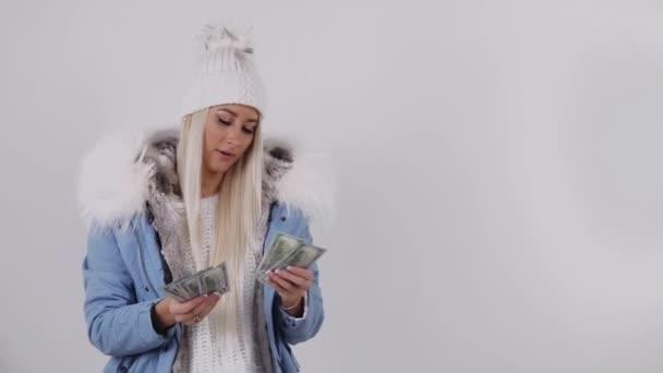 Novoroční přání splní, koncept. Mladá dívka utrácí peníze a je dárky na Vánoce