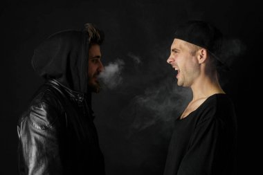 Bad habit, smoking in a public place. Two Young man blowing smoke to join it in one cloud at black studio background. Friends and vape addiction concept.