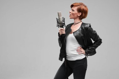 Portrait of rock singer wearing leather jacket and keeping static mic, sings a song loudly on grey background. Concept of rock music and rave