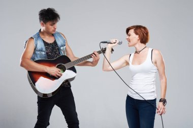 Musical artists sing and play acoustic guitar. Contemporary cover band. Isolated over grey background. Woman with microphone sing loudly