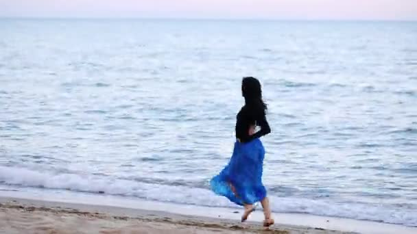 long haired young ballerina in blue skirt runs and jumps in ballet poses along calm sea beach in evening slow motion