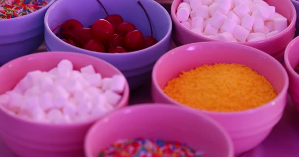 motion along delicious seasonings in different small bowls prepared for sweet tasty donuts in cafe extreme close view