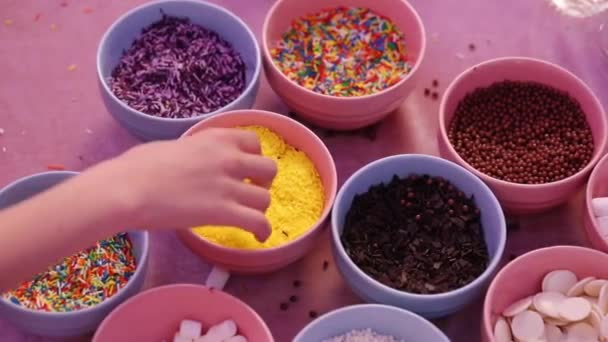 people hands take delicious seasonings from small pink bowls and decorate sweet donuts extreme close view