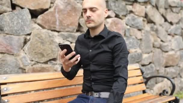 bald cyber criminal looks at smartphone and shows Crypto model in hand sitting on wooden bench closeup