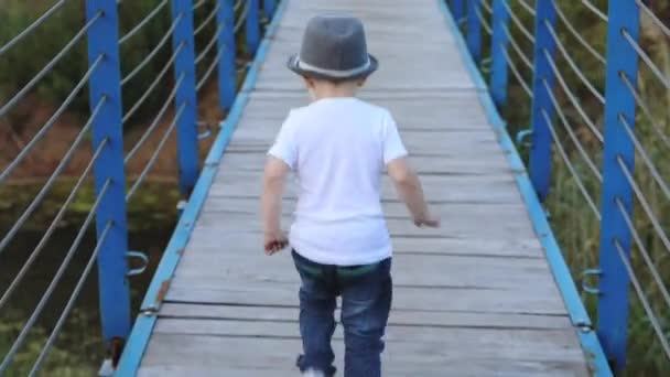 beautiful toddler in t-shirt hat and jeans runs along blue wooden suspension bridge over river close backside view
