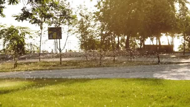 Junge fährt Roller im Park hinter Wasserstrahl
