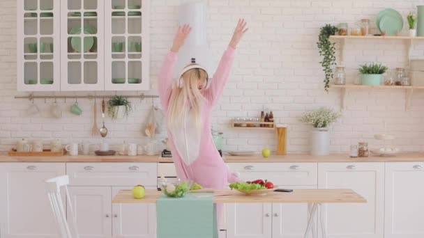 blonde haired girl in kigurumi listens to music in kitchen