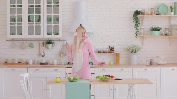 dívka poslouchá hudbu v bílých sluchátkách a připravuje salát
