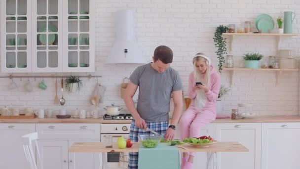 handsome young man cooks and gives sweet apple to girlfriend
