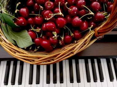 piano keys and basket with cherries