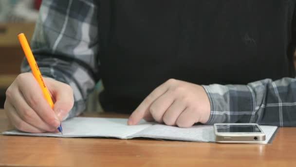 Ismeretlen diák írja a szöveget, tollal a jegyzetfüzet