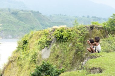 Children sitting on a hill at Mt.Pinatubo