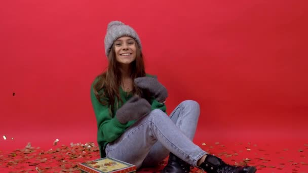girl sitting on the floor on a red background in a hat with confetti and posing for the camera.