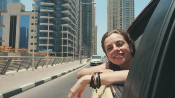 A happy girl sits on the back seat of a car and travels around the city of Dubai.