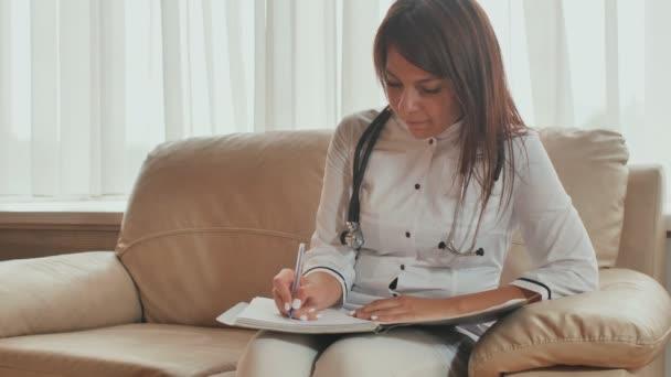 Eine junge Ärztin schreibt verschreibungspflichtige Medikamente und Behandlungsratschläge.