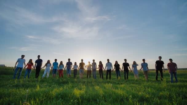 Siluety devatenáct přátel, drželi se za ruce na slunce pozadí