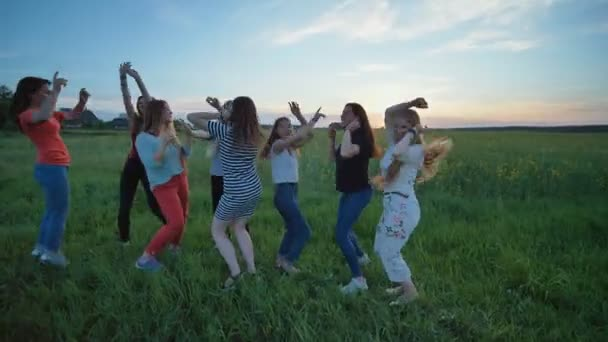 A group of girls are dancing outdoors in the evening.