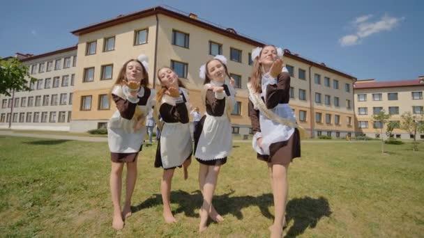 Mädchen in Schuluniformen schicken einen Luftkuss in die Kamera. Russische Absolventen feiern den letzten Schultag.