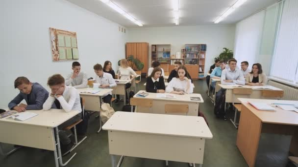Diákok az osztálytermekben ülni iskolában íróasztalok, mielőtt a leckét. Orosz iskola.