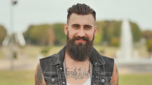Portrait of a brutal and bearded man with tattoos on his shoulders.